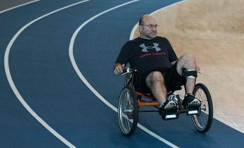 Man cycles around the Lakeshore indoor track on a recumbent bike.