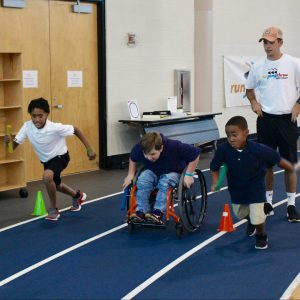 Three children, one using a wheelchair, run around a track.