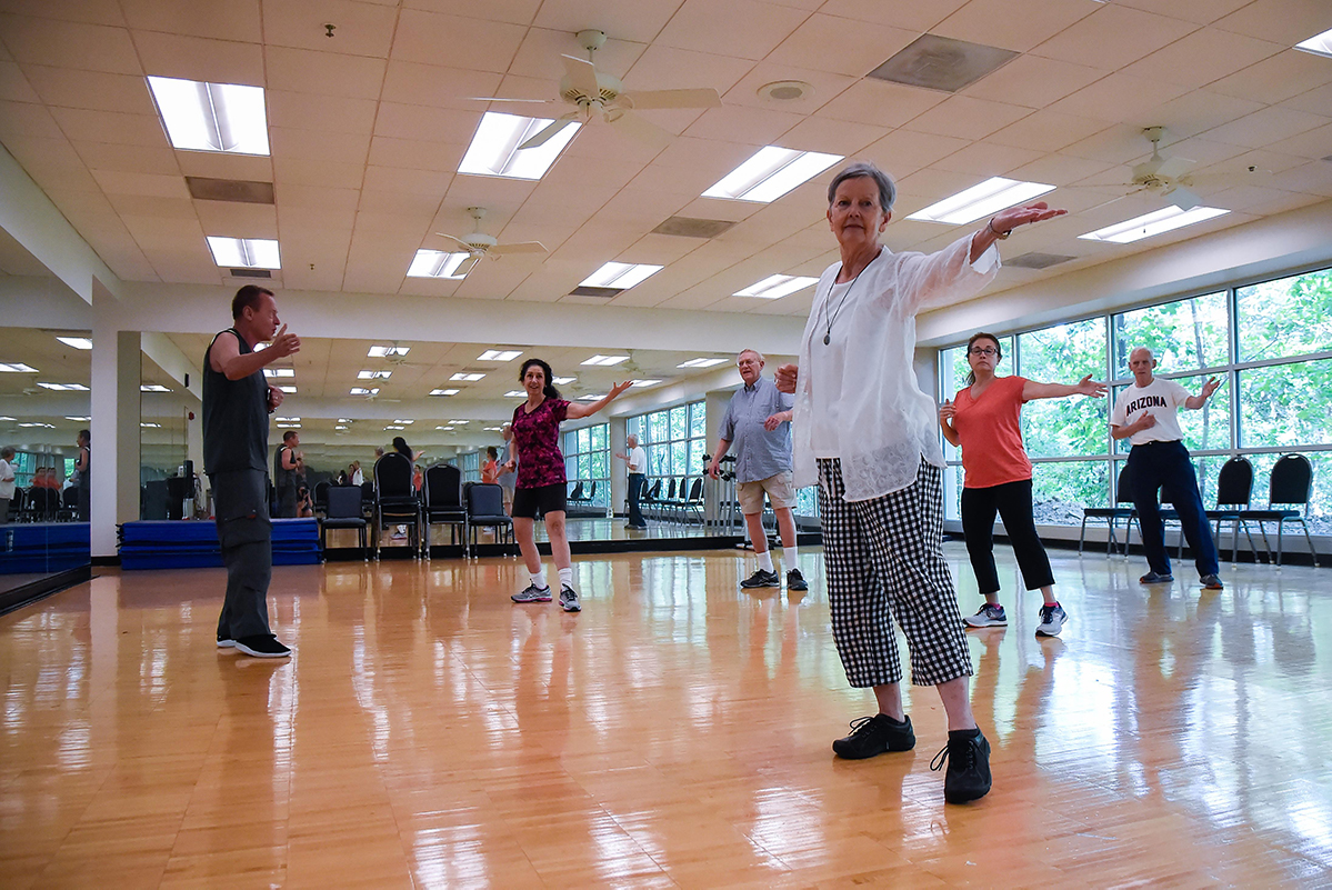 a group of people dancing in a fitness class