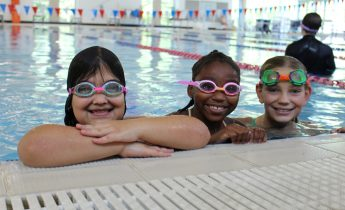 three young girls wearing goggles smile on the edge of the pool