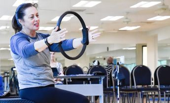 Fitness instructor sits in a chair with her arms extended.
