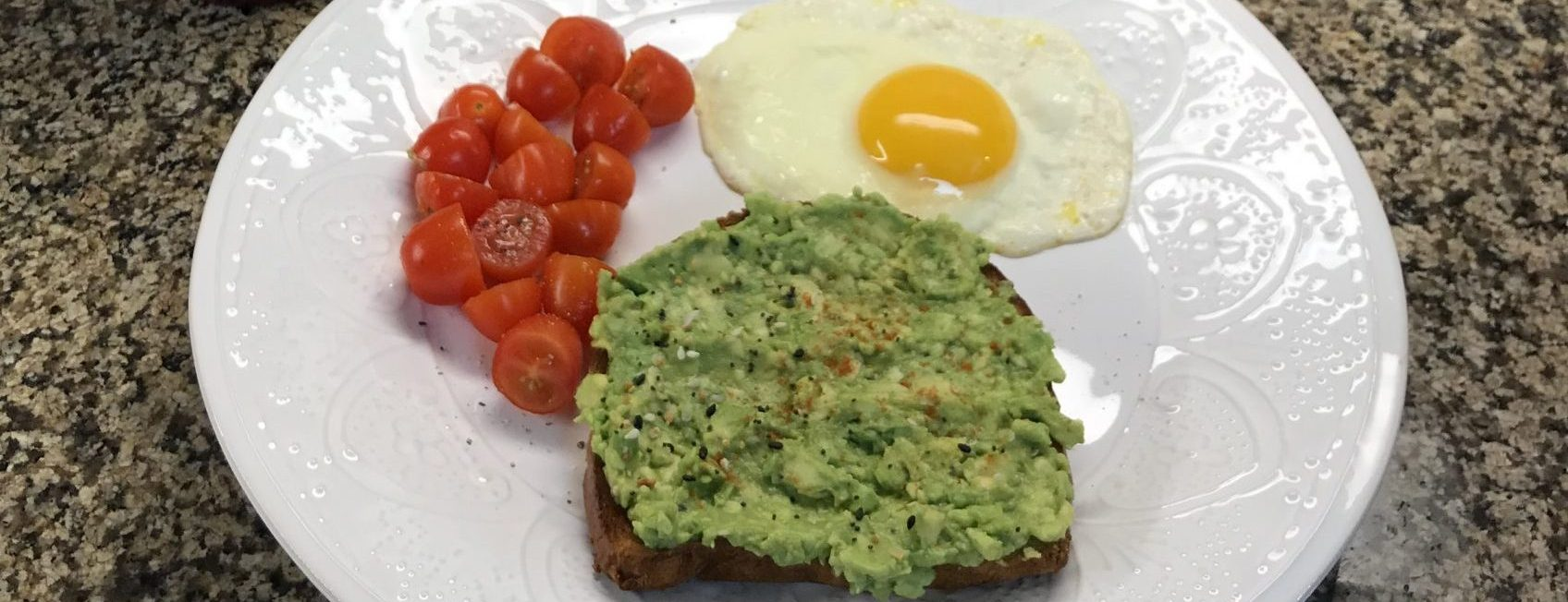 A white plate with cherry tomatoes, avocado toast and a fried egg.
