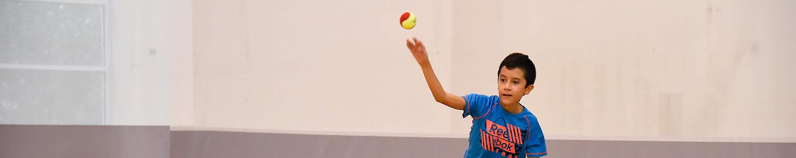 Boy throws tennis ball