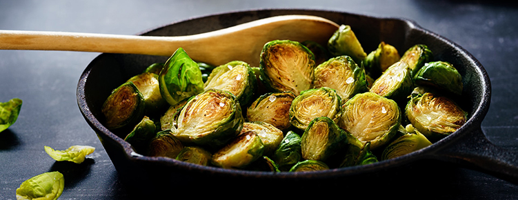 A black skillet filled with Brussels Sprouts