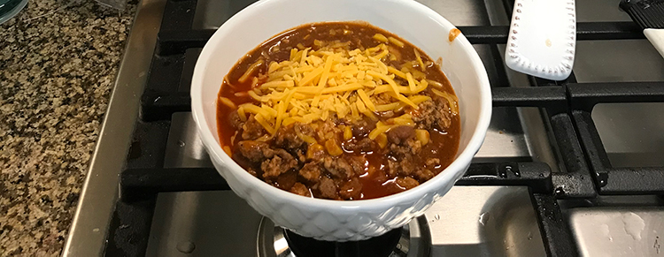 A bowl of chilli with cheese sitting on top of stove.