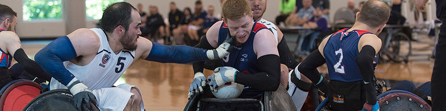 Wheelchair rugby player reaches for ball