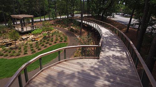 Shaded wood plank bridge overlooking Contemplative Garden