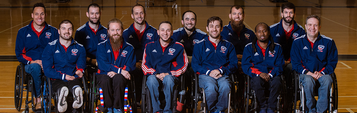 12 USA Wheelchair Rugby players wearing blue jackets smile in 2 lines