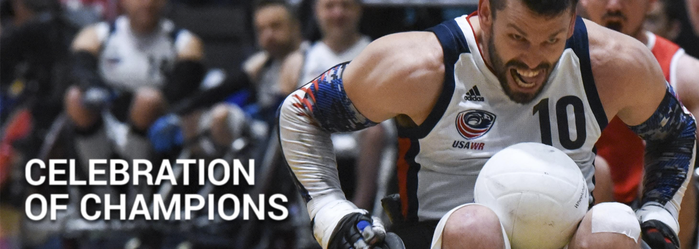 A male wheelchair rugby player wearing a white USA jersey sprints down the court with an intense look on his face.
