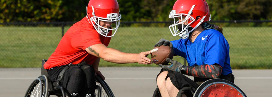 Two wheelchair football players wearing red helmets play on a concrete court outside.