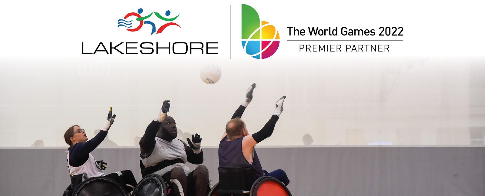 Three wheelchair rugby players reach up to catch a ball underneath the Lakeshore and World Games logo