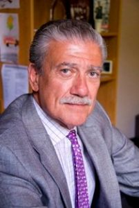 White man with gray hair and mustache wearing a gray suit and purple tie