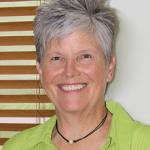 Leila Neighbors, a white woman with short graying hear wearing a green shirt